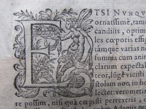 """""""E"""" mayúscula capital, decorada con motivos mitológicos."""