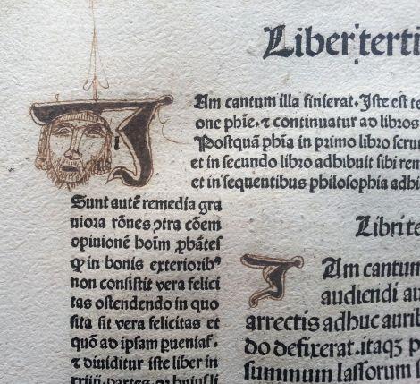 """Un dibujante espontáneo decora (con una J y una cara) la mayúscula capital del texto: Iam cantum illa finiverat…"""" (Acababa ella de recitar su poema…)"""