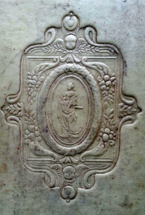 Repujado que representa una mujer con un ancla, rodeada de emblemas de la abundancia (cornucopias)